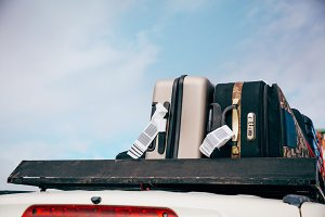 Luggages and Bags arranged on the car roof ready for a trip in sky background