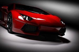 Red fast sports car in spotlight.