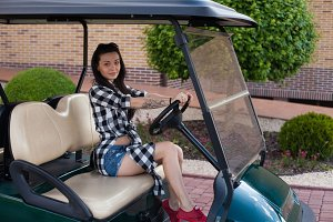 woman is sitting on a golf cart.