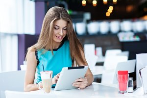 woman using tablet computer in cafe