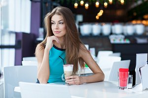 young woman posing in a coffe shop