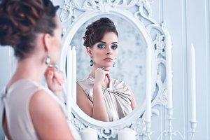 Woman looking in antique mirror