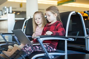 Little girls with laptop at airport