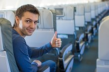 Happy man showing thumbs up inside the aircraft