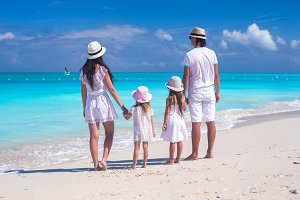 Back view of a young beautiful family on tropical beach