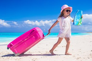 Little adorable girl with big colorful suitcase and a map in hands on tropical beach