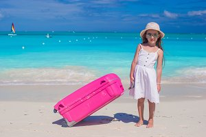 Little adorable girl with big colorful suitcase in hands on white exotic beach