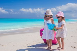 Little lovely girls with big suitcase and a map on tropical beach