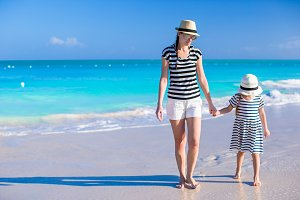 Young mother walking with her daughter along the Atlantic Ocean
