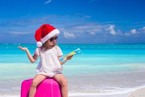 Little girl at Santa hat sitting on a large suitcase with map in hands
