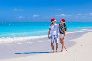 Family in red Santa Hat on beach