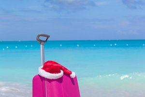 Closeup of pink suitcase and Santa Claus hat background the sea