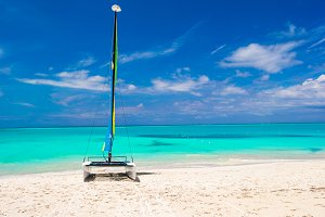 Catamaran with colorful sail on caribbean beach