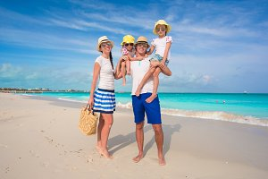 Happy family of four on beach tropical vacation