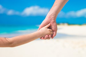 Close up of father and little daughter holding each other hands at beach