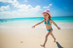 Little girl running along the beach and enjoy summer holidays