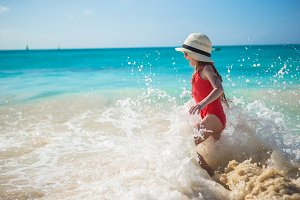 Adorable little girl play with water at beach during caribbean vacation