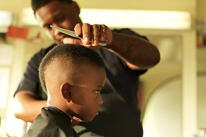 Boy in barbershop getting hair cut