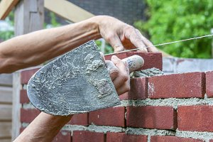 Bricklayer at work with trowel