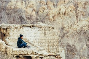Young male traveler sitting on the sand cliff, thinking about something in Leh, Ladakh, India