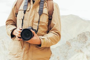 Close-up of travel photographer journalist holding a dslr camera in mountain background