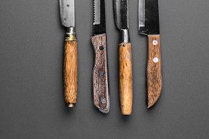 collection of various kitchen knives on a grey background