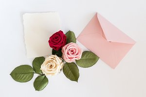 Pink envelop with white card and roses. Flat lay.