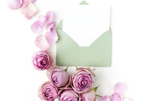 Paper envelop with white card and pink roses. Flat lay, top view