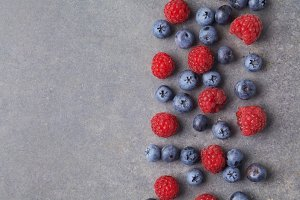 Blueberries and raspberries in a bowl on rusty grey background. Top view