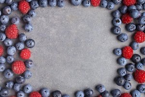 Blueberries and raspberries frame on rusty grey background. Top view