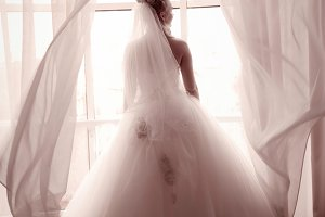 bride standing beside a large window