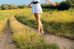 young happy girl walking on meadow