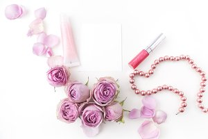 flat lay composition with cosmetics and pink rose flowers. Top view