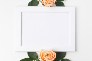 Decorative frame with orange roses and green leaves. Flat lay. Top view