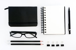 Top view of blank note book, eyeglasses and pencils. Flat lay