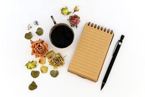 Cup of coffee, sketchbook, pencil and dried flowers. Flat lay, top view