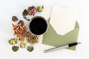 Cup of coffee, blank paper in the envelope, pen and flowers. flat lay, top view