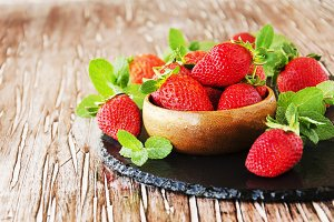 ripe red raspberries and strawberries in wooden bowl, selective focus