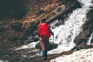 traveler with red backpack hiking
