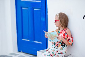 Little girl with map of island outdoors in old streets an Mykonos. Kid at street of typical greek traditional village with white walls and colorful doors on Mykonos Island, in Greece