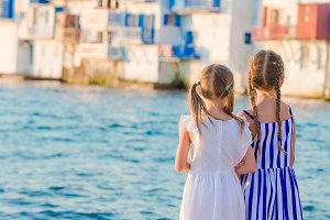 Adorable little girls at Little Venice the most popular tourist area on Mykonos island, Greece. Back view of beautiful kids look at Little Venice background.
