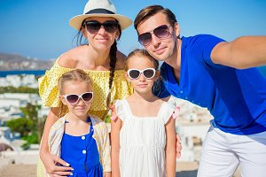 Family vacation in Europe. Parents and kids taking selfie background Mykonos town in Greece