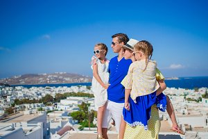 Family vacation in Europe. Parents and kids looking at the cityscape of Mykonos island in Greece