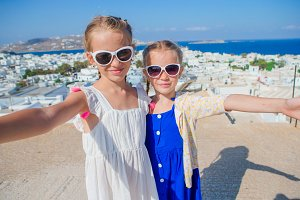 Two girls in blue dresses taking selfie photo outdoors. Kids background of typical greek traditional village with white walls and colorful doors on Mykonos Island, in Greece