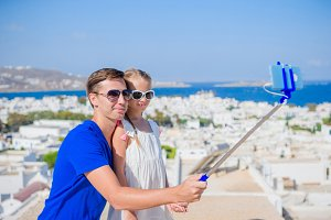 Family vacation in Europe. Father and daughter taking selfie background Mykonos town in Greece by their smartphone
