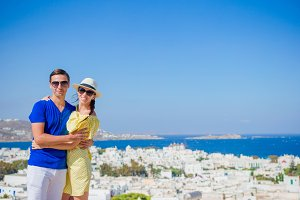 Beautiful young couple at Mykonos island, Cyclades. Tourists enjoy their greek vacation in Greece background famous Mykonos village