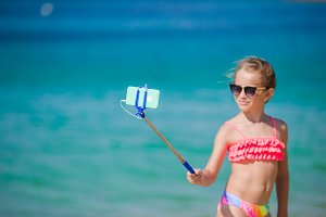 Little girl taking selfie portrait with her smartphone on the beach. Adorable model making selfportrait background beautiful sea.