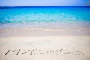 Word Mykonos handwritten on sandy beach with soft ocean wave on background