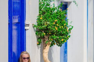 Adorable little girl sitting in front of blue door outdoors at typical greek traditional village on Mykonos in Greece