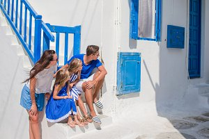 Family vacayion in Europe. Parents and kids at street of typical greek traditional village with white walls and colorful doors on Mykonos Island, in Greece